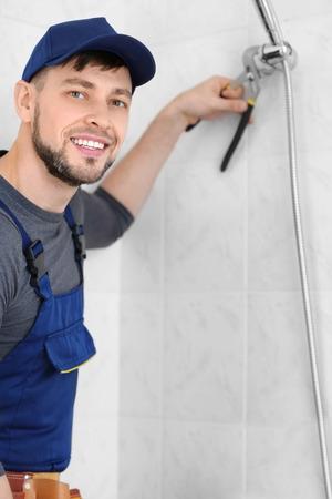 Plumber repairing shower head in bathroom Imagens