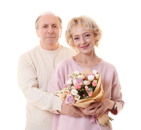 Happy senior couple with bouquet of flowers isolated on white Stock Photo