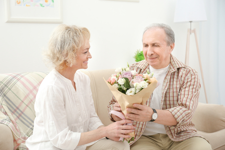 Senior man giving flowers to his wife at home Stock Photo