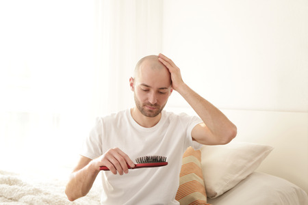 Hair loss concept. Young man with comb at home Stock Photo