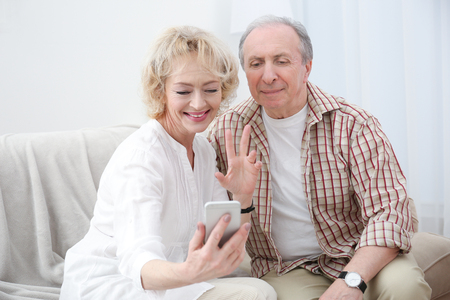 Happy senior couple sitting on sofa at home