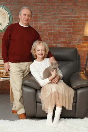 Portrait of happy senior couple with cat at home