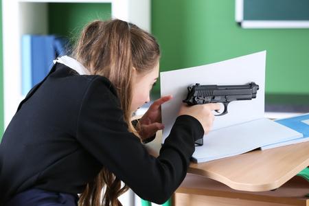 Teenage girl taking aim from gun in classroom Stock Photo