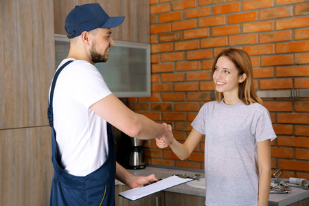 Plumber and woman shaking hands at home