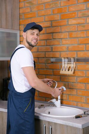 Plumber repairing faucet in kitchen