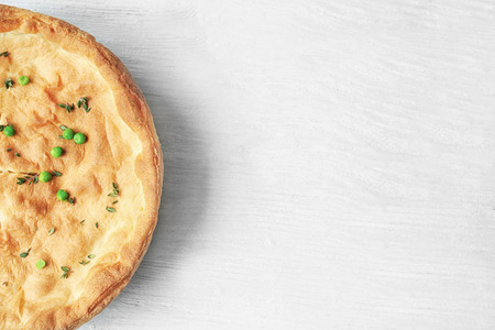 Tasty chicken pot pie on white wooden table