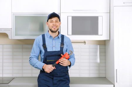 Plumber in blue uniform holding pipe wrench at kitchen