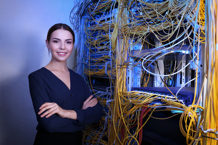 Beautiful young engineer in server room