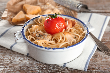 Bowl with tasty chicken spaghetti on wooden table