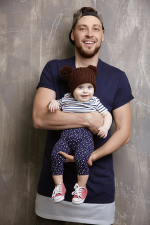 Father posing with cute baby daughter on grunge background 版權商用圖片