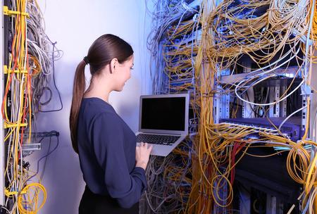 Beau jeune ingénieur avec ordinateur portable dans la salle des serveurs Banque d'images