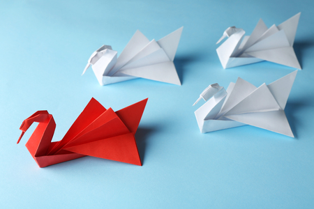 Boss vs Leader concept. White origami birds behind red one on blue background Stockfoto