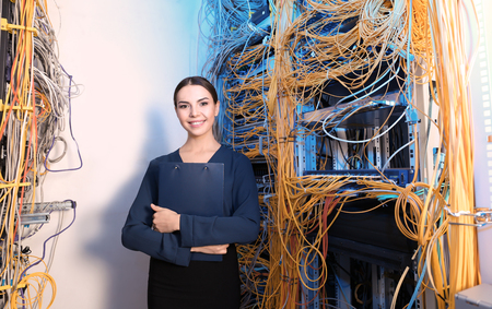 Beautiful young engineer with clipboard in server room Imagens