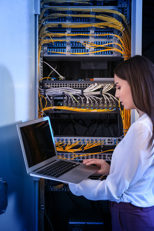 Beautiful young engineer with laptop in server room Stock Photo