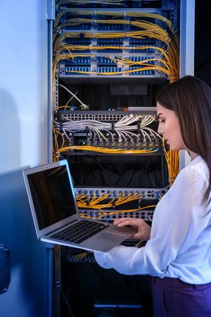 Hermosa joven ingeniero con portátil en la sala de servidores
