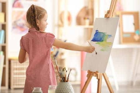 Schattige kleine kunstenaar schilderij foto in studio Stockfoto