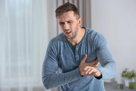 Man having a heart attack at home Stock Photo
