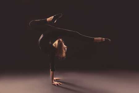 Young girl doing gymnastics on dark background Imagens