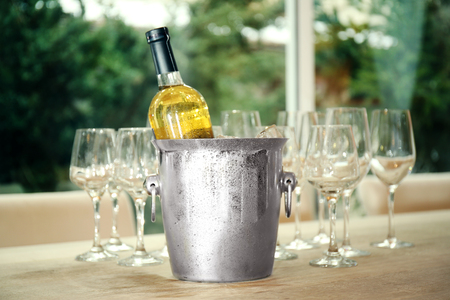 Wine bottle in bucket with ice and glasses on table 版權商用圖片