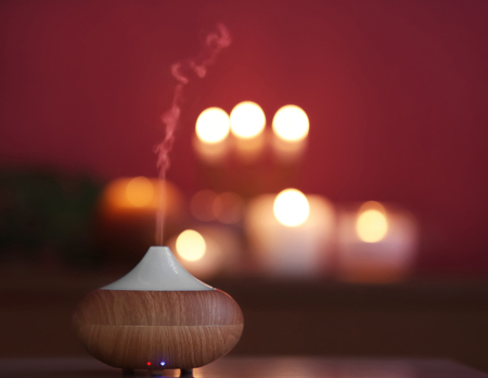 Aroma oil diffuser on blurred candlelight background Standard-Bild