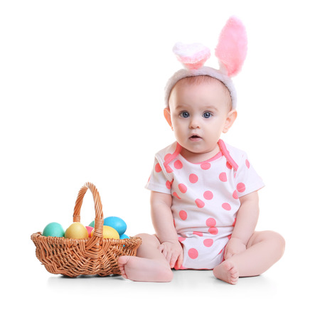 Cute funny baby with bunny ears and basket full of Easter eggs on white background