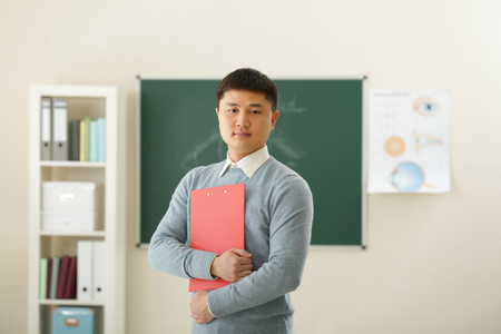 Handsome Asian teacher with clipboard in classroom