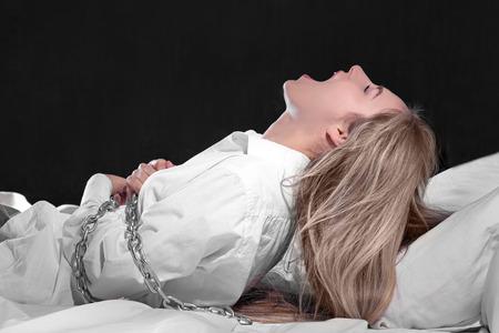 Chica atada con cadena en la cama. Concepto de parálisis del sueño