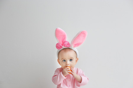 Cute funny baby with bunny ears and Easter egg on light background Reklamní fotografie