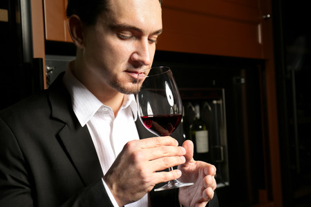 Man with glass of red wine in modern cellar Imagens