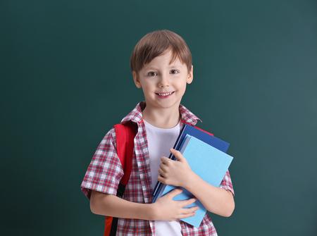 Cute little boy on school blackboard background