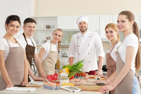 Chef masculin et groupe de personnes aux cours de cuisine