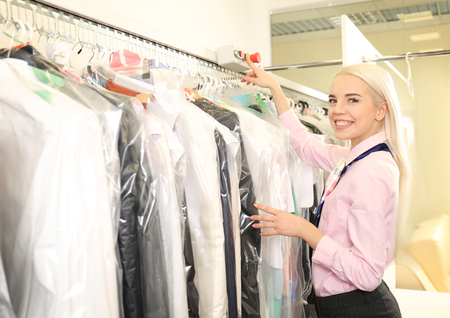 Female laundry worker pushing button on  rack at dry-cleaning