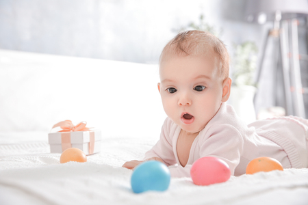 Cute little baby with Easter eggs lying on bed at home