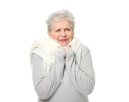 Portrait of elderly woman feeling cold on white background