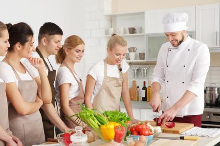 Mannelijke chef-kok en groep mensen bij kooklessen Stockfoto