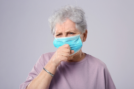 Portrait of coughing elderly woman wearing protective mask on grey background Фото со стока