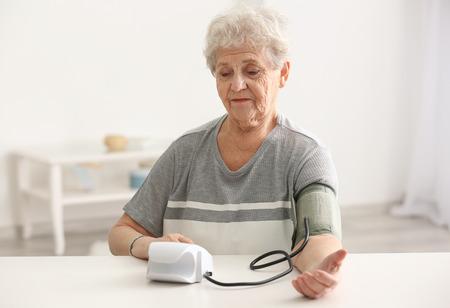 Ältere Frau, die den Druck mit dem digitalen Blutdruckmessgerät misst, während sie am Tisch sitzt