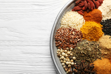 Tray with mix of different spices on wooden table
