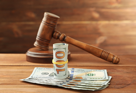 Money and judges gavel on wooden background