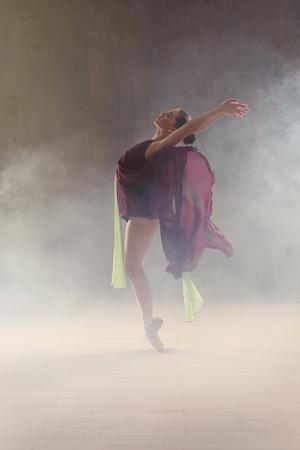 Young beautiful ballerina dancing in studio with smoke effect 版權商用圖片