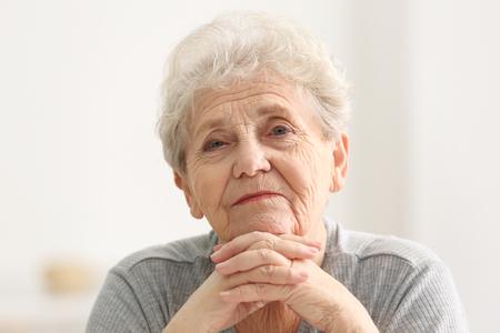 Retrato de anciana apuntalando la cara con las manos en la sala de luz Foto de archivo