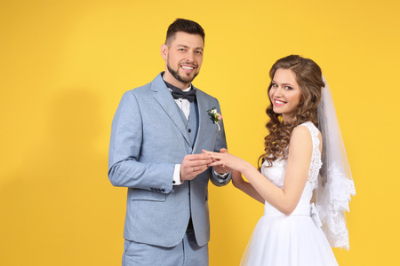 Happy wedding couple on color background Stock Photo