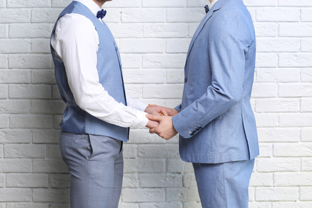 Happy couple holding hands together on brick wall background