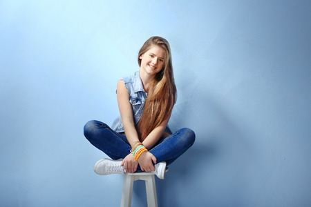 Pretty teenager girl posing on color background Stockfoto