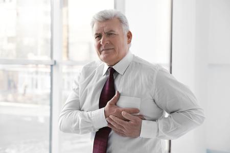 Homme souffrant de douleur thoracique souffrant d'une crise cardiaque au bureau Banque d'images