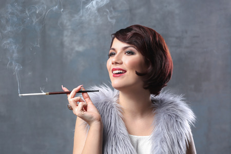 Young woman smoking with cigarette holder on color background