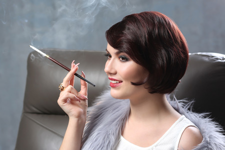 Young woman sitting in armchair and smoking with cigarette holder on color background 免版税图像