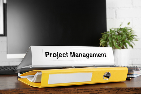 Folder with label PROJECT MANAGEMENT on wooden table