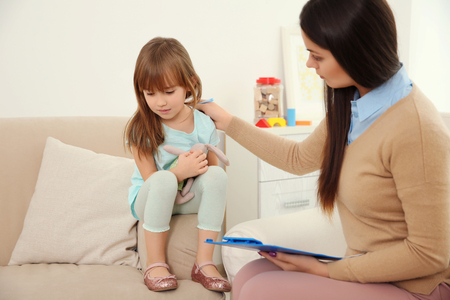 Young child psychologist working with little girl Stockfoto