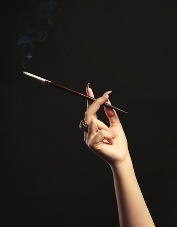 Female hand with cigarette holder on dark background Stockfoto